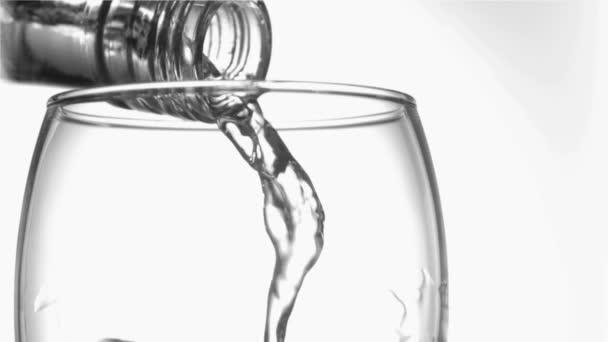 Filet d'eau dans un super slow motion qui coule du verre goulot dans un verre tumbler — Vidéo