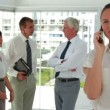 Businesswoman on the phone with colleagues in background — Stock Video