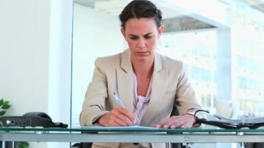 Woman in suit writing while sitting at her desk — Stock Video