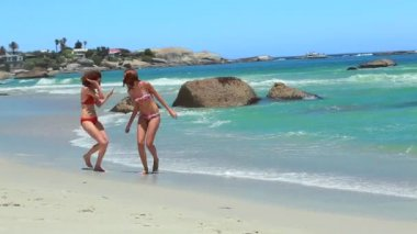 Two women running together on the beach shore — Vidéo