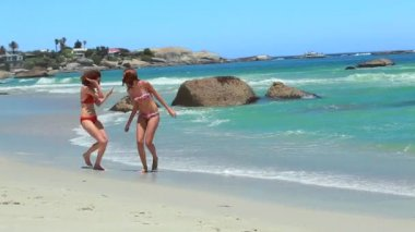 Two women running together on the beach shore — Stok video