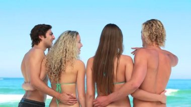 Four pals embrace each other at the beach — Stock Video