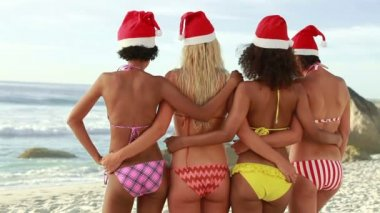 Four girls embracing each other while wearing santa hats — Stock Video