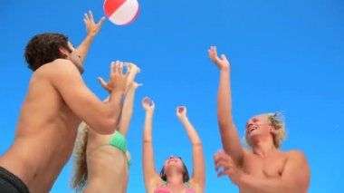 Four friends playing with an inflatable beach ball — Stock Video