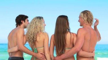 Fyra vänner omfamnar varandra på stranden — Stockvideo