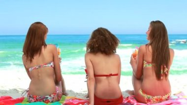 Three women sitting on towels on the sand — Stock Video