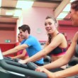 Two women chatting while using exercise bikes — Stock Video #21065239