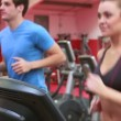 Woman and man jogging on treadmills — Stock Video #21065401