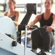 Two women drawing on row machine — Stockvideo