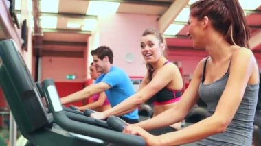 Two women chatting while using exercise bikes — Stock Video