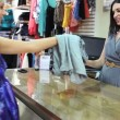 Woman buying clothes at till — Stock Video