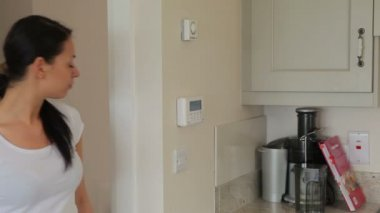 Woman turning on home alarm system — Stock Video
