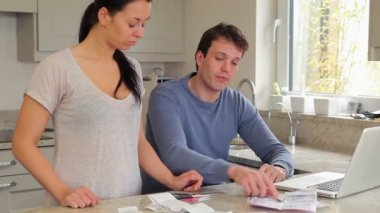 Couple stressing over finances with woman cutting credit card — Stock Video
