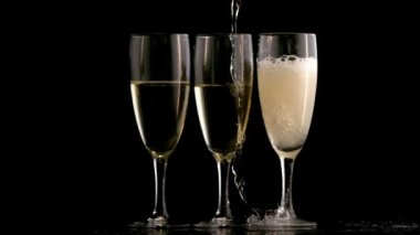 Three champagne flutes topped up — Stock Video