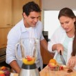 Couple putting fruits into a blender — Stock Video