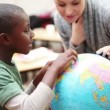 Pupil and teacher looking at a globe — Stock Video