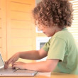 Boy typing on a laptop and waves at the camera — Stock Video