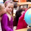 Stock Video: Happy pupils looking at globe