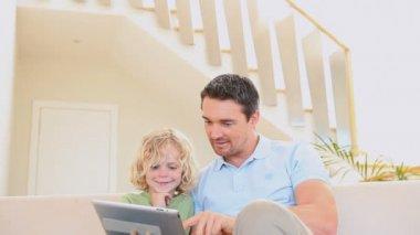 Muž pomocí tablet, zatímco jeho syn se dívá — Stock video
