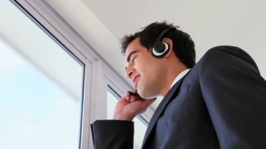 Man looking outside while calling with a headset — Stock Video