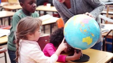 Teacher showing a globe to her pupils — Stock Video