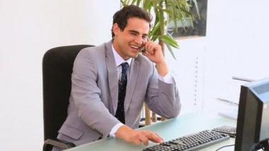 Homem de negócios se senta na frente do computador — Vídeo Stock