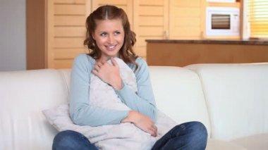 Mulher senta-se no sofá com as pernas dobradas — Vídeo Stock
