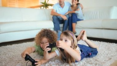 Children playing video games to the on a carpet — Stock Video