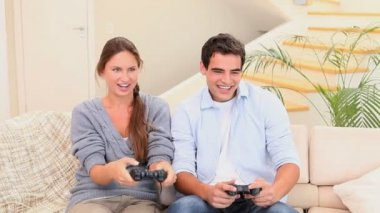 Man och kvinna som sitter i soffan spelar konsolspel — Stockvideo