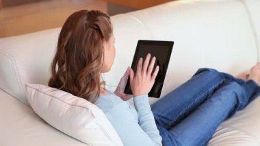 一个女人躺在沙发上,一个在她手中的平板 — 图库视频影像