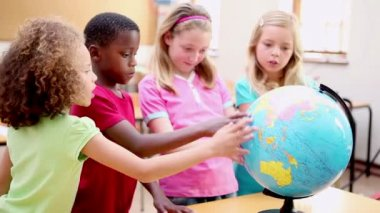 Smiling pupils looking at a globe — Stock Video