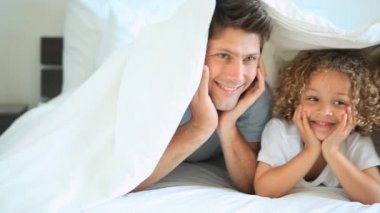 A family under the bed sheets smiling — Stock Video