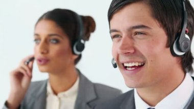 Smiling call centre agents using headsets — Stock Video