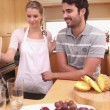 Lady giving a smoothie to her boyfriend - Stock Photo