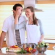 Husband tasting his wife's cooking with a spoon - Stock Photo