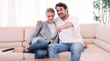 Couple souriant, assis sur le canapé en regardant la télévision — Vidéo