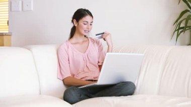 Pani siedząca na kanapie przy użyciu jej karty kredytowej — Wideo stockowe