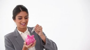Businesswoman putting money in a piggy-bank — Stock Video