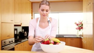 Young woman placing a bowl of fruit on the worktop — Stock Video