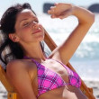 Brunette sitting on a deck chair — Stock Video