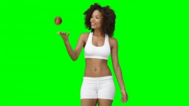 A woman stands while tossing an apple up into the air and catching it — Stock Video