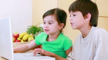 Happy children grimacing in front of a laptop — Stock Video