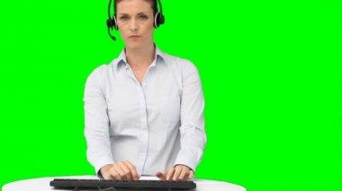 Een vrouw met een headset te typen op haar toetsenbord — Stockvideo