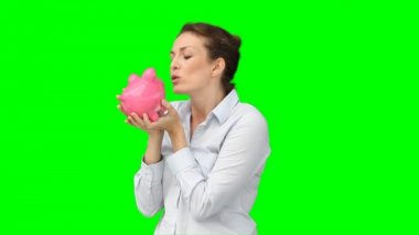 A woman kissing and cherishing her piggy-bank — Stock Video