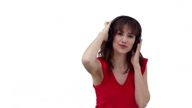 Woman dancing as she listens to music through headphones against a white background