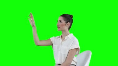Seated woman scrolling through icons on a virtual touchscreen — Stock Video