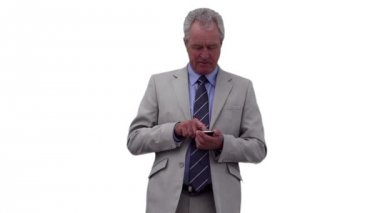 Serious businessman dialing on his phone while looking around him — Stock Video