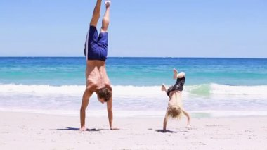 Smiling father doing handstands with his son — Stock Video