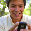 Smiling man using a cellphone - Stock Photo