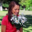 Stock Video: Happy womlaughing while holding flowers